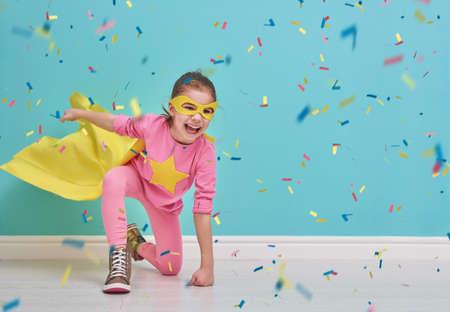작은 아이는 슈퍼 히어로을한다. 밝은 파란색 벽의 배경에 아이. 여자 색종이를 던지고있다. 노란색, 분홍색과 터키석 색. 스톡 콘텐츠