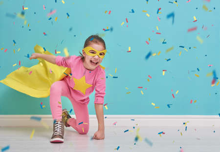 Little child plays superhero. Kid on the background of bright blue wall. Girl is throwing confetti. Yellow, pink and  turquoise colors. Stock Photo