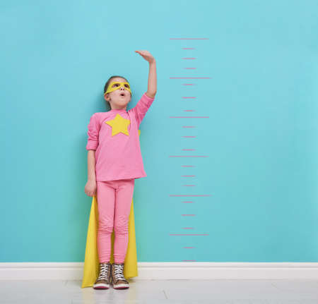 Little child plays superhero. Kid measures the growth on the background of bright blue wall. Girl power concept. Yellow, pink and  turquoise colors. Stock Photo