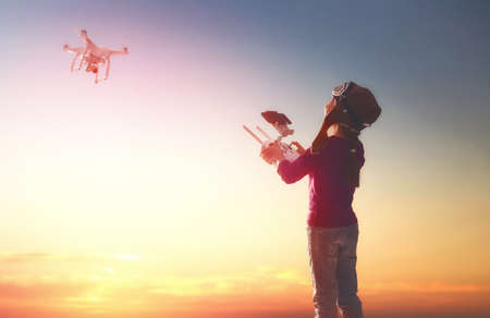 Little girl is operating the drone by remote control in the park. Kid is playing with quadrocopter outdoors. Stock Photo