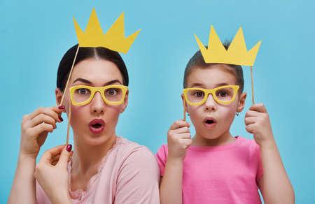 밝은 파란색 벽의 배경에 재미 가족. 어머니와 종이 액세서리와 그녀의 딸 소녀. 엄마와 아이는 크라운 안경을 들고 막대기에 있습니다.