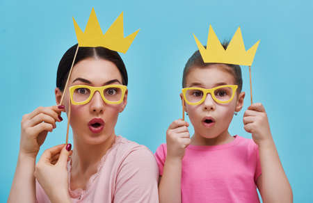 Funny family on a background of bright blue wall. Mother and her daughter girl with a paper accessories. Mom and child are holding crowns glasses and on stick.