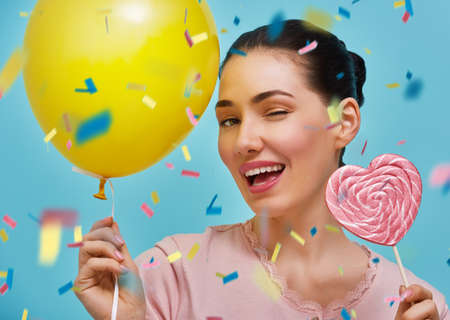 Funny young woman on background of bright blue wall. Beautiful girl is having fun with balloon, confetti and lollipop. Yellow, pink and turquoise colors. Stok Fotoğraf - 70913011