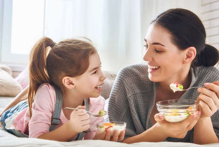 niña comiendo: Happy loving family. Mother and her daughter child girl are eating fruity salad on the bed in the room.