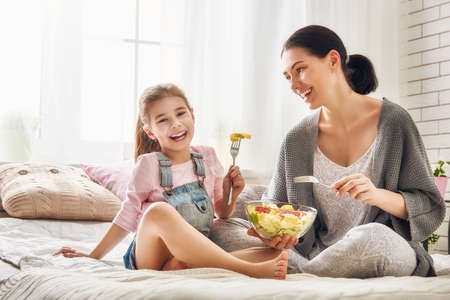 eating salad: Happy loving family. Mother and her daughter child girl are eating salad on the bed in the room. Stock Photo