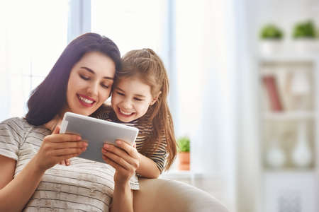 Happy loving family. Young mother and her daughter girl play in kids room. Funny mom and lovely child are having fun with tablet.