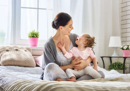Happy loving family. Young mother are playing with her baby girl in the bedroom. Mom and child are having fun on the bed.