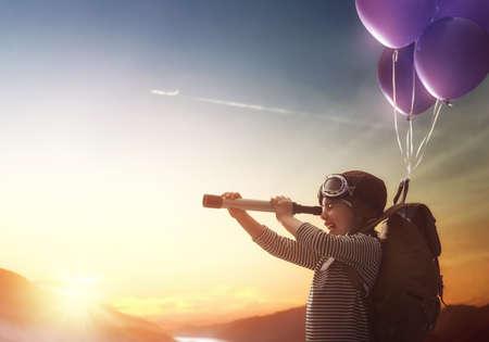 旅行の夢!夕日の背景に風船で飛んでの子。