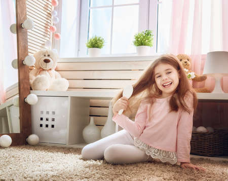 Cute little child is combing near mirror. Happy girl is having fun in kids room at home. Stock Photo