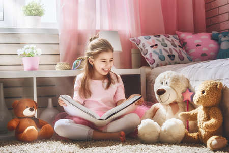 Cute little kid girl is reading a book at home. Funny lovely child having fun in kids room.