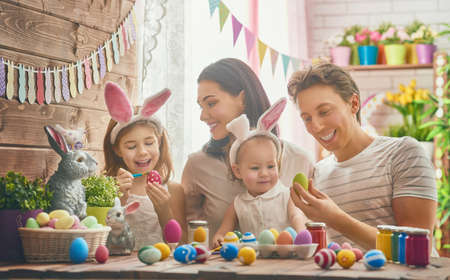 little table: Mother, father and daughters are painting eggs. Happy family are preparing for Easter. Cute little child girl wearing bunny ears.