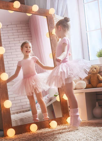 Cute little girl dreams of becoming a ballerina. Child in a pink tutu dancing in a kids room. Stock Photo - 72480038