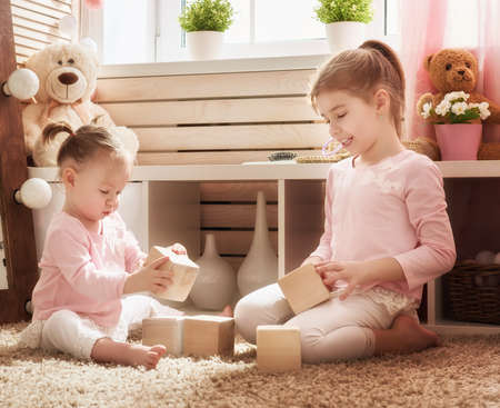 Two cute little children are playing with blocks. Happy girls at home. Funny lovely sisters are having fun in kids room. Stock Photo