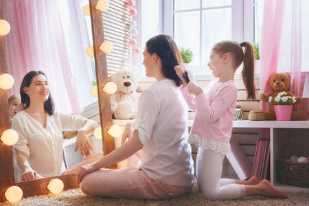 Happy loving family. Cute little girl is combing her mothers hair sitting near mirror in the children room.