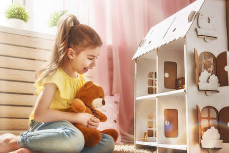 행복 한 소녀는 집에서 인형의 집과 테디 베어와 함께 재생됩니다. 재미 사랑스러운 아이는 아이 방에 재미입니다. 스톡 콘텐츠