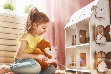Gelukkig meisje speelt met poppenhuis en teddybeer thuis. Grappig mooi kind is plezier in de kinderkamer.
