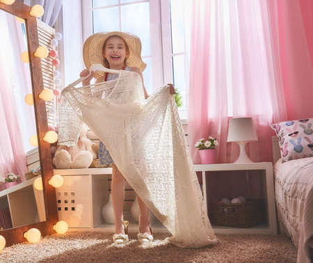 large: Happy girl dresses up at home. Funny lovely child is having fun in kids room.
