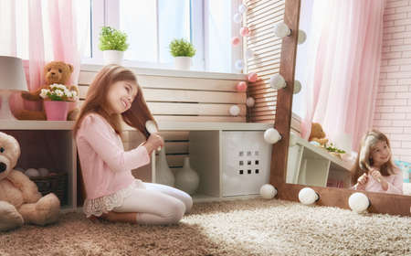 comb: Cute little child is combing near mirror. Happy girl is having fun in kids room at home.
