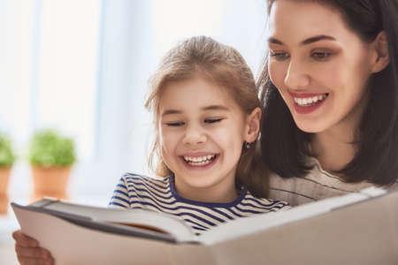 Jolie jeune mère et sa fille mignonne lisent un livre. Apprendre à lire à la maison.