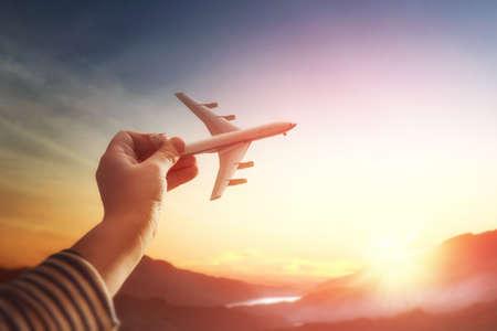 어린이는 석양과 여행의 꿈에서 장난감 비행기를 가지고 노는. 작은 비행기와 손을 닫습니다.