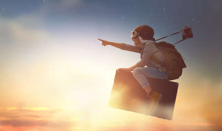 Dreams of travel! Child flying on a suitcase against the backdrop of sunset. Stock Photo - 72447266