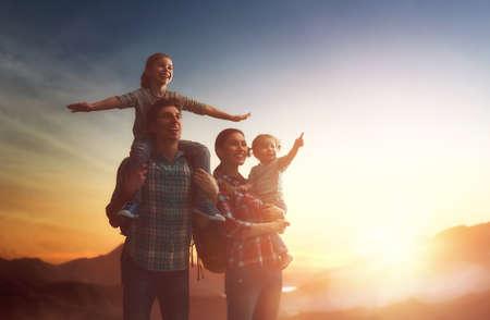 Glückliche Familie bei Sonnenuntergang. Vater, Mutter und zwei Kinder Töchter, die Spaß haben und genießen Reise. Das Kind sitzt auf den Schultern seines Vaters.