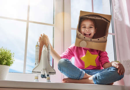 Child girl in an astronaut costume with toy rocket playing and dreaming of becoming a spacemen. Portrait of funny kid near windows. Banco de Imagens