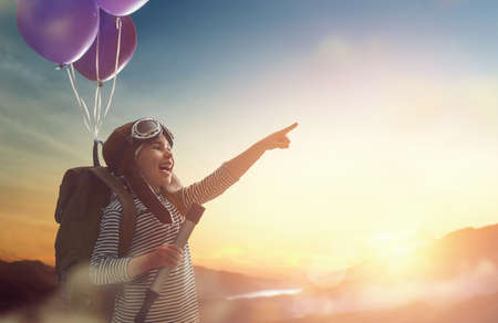 Dreams of travel! Child flying on balloons against the backdrop of a sunset. Stock Photo