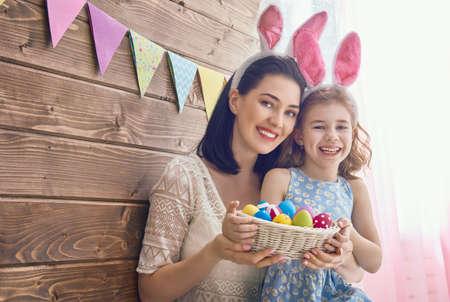 Moeder en haar dochter met het schilderen van eieren. Gelukkige familie vieren Pasen. Leuk weinig kind meisje draagt ??bunny oren.