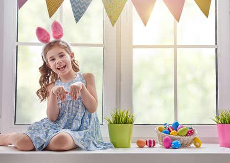 Pequeño que desgasta lindo niño oídos del conejito. Niña sentada en la ventana con una canasta con huevos. Kid se ríe y disfruta de la primavera y el día de fiesta. Foto de archivo - 72996369