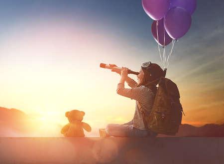 작은 아이는 석양을 찾고 있습니다. 배낭과 젊은 여행자.