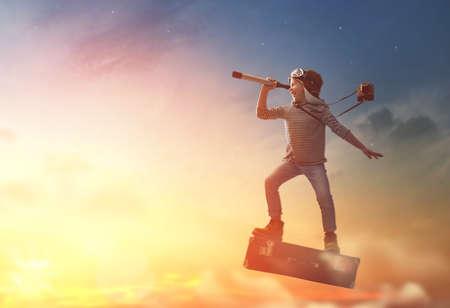 Sogni del viaggio! Bambino che vola su una valigia sullo sfondo del tramonto.