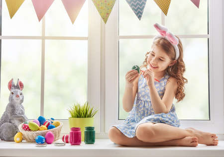 Cute little child wearing bunny ears. Girl sitting on the window. Kid is painting eggs.