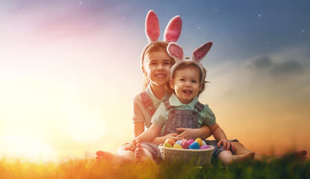 Two cute little children wearing bunny ears. Girls are sitting on the lawn. Kids with Easter eggs in the rays of the setting sun. Stock Photo