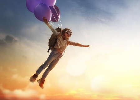 Sueños de viaje! Niño que vuela en los globos contra el telón de fondo de una puesta de sol. Foto de archivo - 73276660
