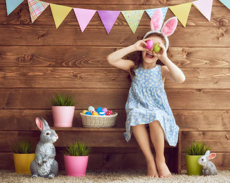 Cute little child wearing bunny ears on Easter day. Girl holding basket with painted eggs. Stock fotó