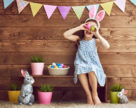 Piccolo bambino sveglio con le orecchie coniglio il giorno di Pasqua. Ragazza che tiene cestino con uova dipinte. Archivio Fotografico - 73276657