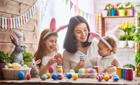A mother and her daughter are painting eggs. Happy family are preparing for Easter. Cute little child girl wearing bunny ears. 免版税图像