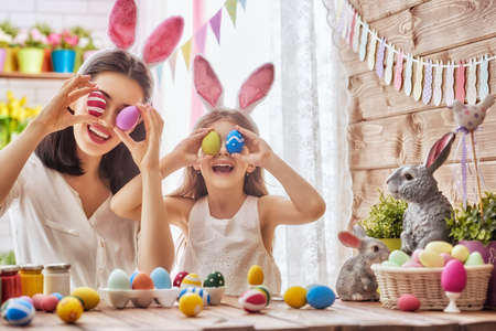 Mother and her daughter painting eggs. Happy family preparing for Easter. Cute little child girl wearing bunny ears.