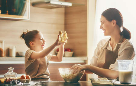 massage enfant: Mother and child daughter girl are cooking cookies and having fun in the kitchen. Banque d'images