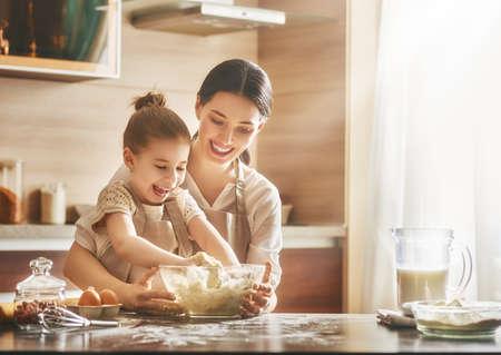 Het gelukkige houdende van familie bereidt samen bakkerij voor Moeder en kookt koekjes en heeft pret in de keuken. Stockfoto