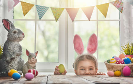 Happy Easter! Cute little child girl wearing bunny ears on Easter day. Child girl laughs and enjoys spring and a holiday.