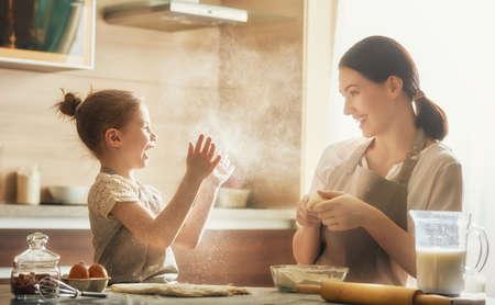 Glückliche liebevolle Familie bereiten Bäckerei zusammen. Mutter und Kind, Tochter Mädchen kochen Cookies und Spaß in der Küche. Hausgemachte Speisen und kleiner Helfer.
