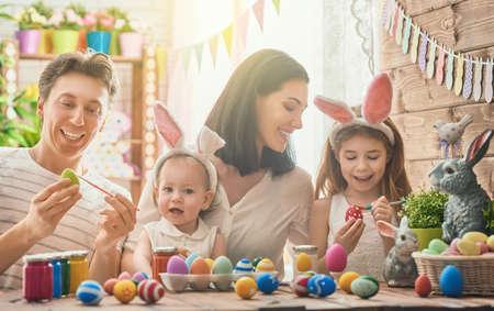 Pai, mãe e filhas estão pintando ovos. A família feliz está se preparando para a Páscoa. menina da criança pequena bonito que veste as orelhas do coelho. Imagens - 73897816