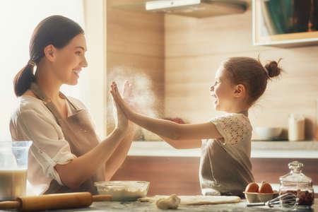 행복 한 사랑 가족이 함께 빵집을 준비하고있다. 어머니와 자식 딸 소녀 쿠키를 요리 부엌에서 재미 있습니다. 집에서 만든 음식과 작은 도우미. 스톡 콘텐츠