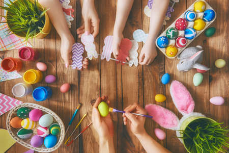 table: A mother, father and their child painting eggs. Happy family preparing for Easter.