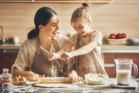 biscuits: Happy loving family are preparing bakery together. Mother and child daughter girl are cooking cookies and having fun in the kitchen. Homemade food and little helper.