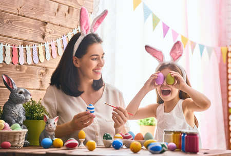 table: Mother and her daughter painting eggs. Happy family preparing for Easter. Cute little child girl wearing bunny ears.