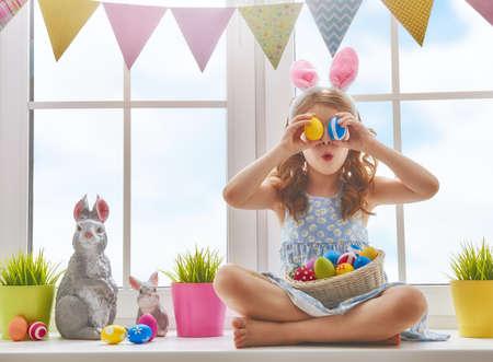 かわいい小さな子ウサギの耳を身に着けています。ペイントされた卵を持つウィンドウに座っている女の子。 写真素材