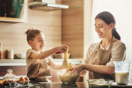 massage enfant: Happy loving family are preparing bakery together. Mother and child daughter girl are cooking cookies and having fun in the kitchen. Homemade food and little helper.